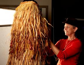 Artist Ruth Port with her weaving titled He Kakahu o Papatuanuku.